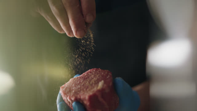 vídeos de stock, filmes e b-roll de slo mo. professional chef sprinkles pepper on steak in a commercial kitchen - frito