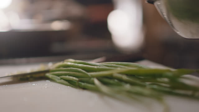 professional chef sprinkles water on scallions in a commercial kitchen before slicing - schüssel stock-videos und b-roll-filmmaterial