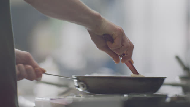 professional chef stirs eggs in a pan while cooking in a commercial kitchen at a diner. - garkochen stock-videos und b-roll-filmmaterial