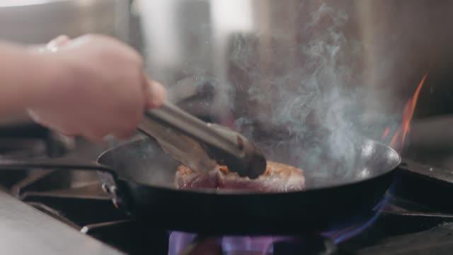 slo mo. professional chef uses tongs to add tuna steaks to a cast iron pan - 獲った魚点の映像素材/bロール
