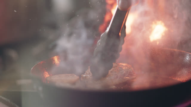 slo mo. professional chef uses tongs to flip over tuna steak to see if it's cooked - raw food stock videos & royalty-free footage