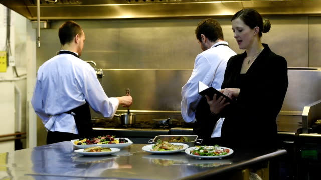 professional culinary team in a commercial kitchen - caterer stock videos and b-roll footage