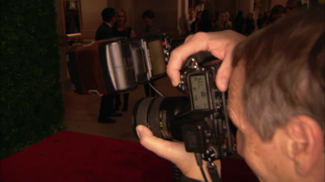 professional digital camera in hands of unidentifiable photographer taking pictures at red carpet event - digital camera stock videos and b-roll footage