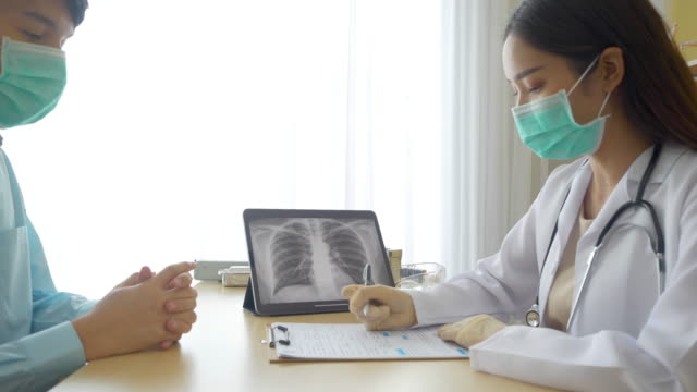 professional doctor wear surgical mask explaning patient and showing screen laptop with lung x-ray image.  physician wearing gown talking suspected patients infected with corona virus, covid 19 in clinic hospital ward - torso stock videos & royalty-free footage