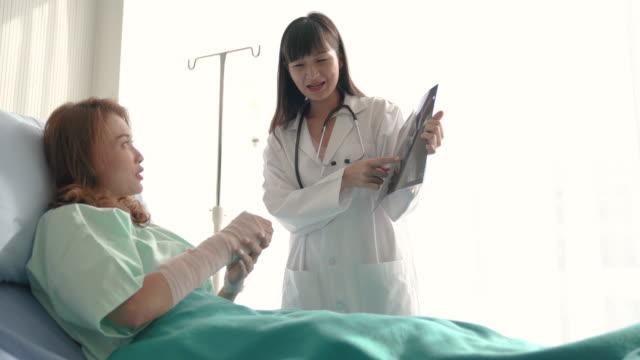 病院で車椅子に座っている間、医師が手を包帯で折りたたんで女性にx線画像を解釈する専門医 - 骨折点の映像素材/bロール