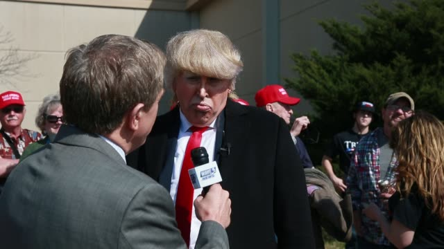 professional donald trump impersonator dustin gold speaks to a journalist from a local tv station outside the kentucky exposition center where united... - doppelgänger stock-videos und b-roll-filmmaterial