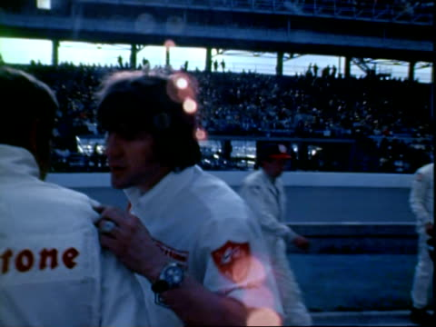 CU professional driver BOBBY UNSER wearing racing jumpsuit while standing in pits and talking with younger brother and fellow professional race car...