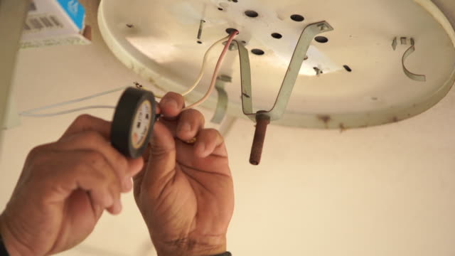 professional electrician twisting bulb installing light - changing lightbulb stock videos & royalty-free footage