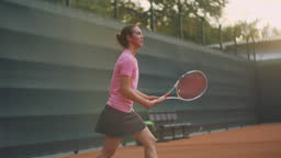 Professional equipped female beating hard the tennis ball with tennis racquet. Female tennis player in action during game. She is wearing unbranded sport clothes.