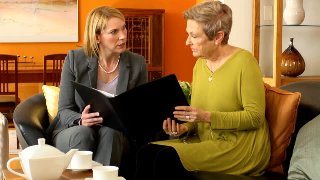 vídeos de stock, filmes e b-roll de profissional explica documentos para mulher sênior - testamento