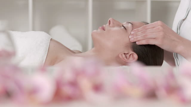 vídeos de stock, filmes e b-roll de hd dolly: profissionais de massagem facial no spa center - tratamento em spa