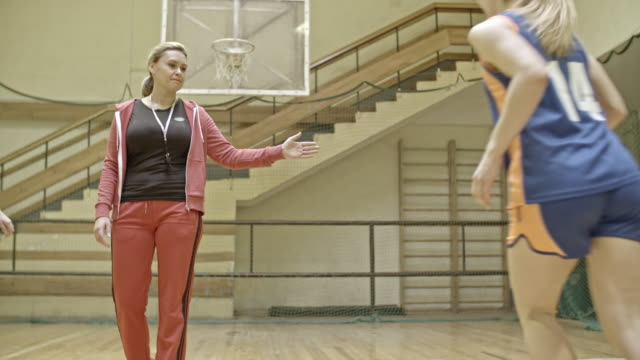 Professional female basketball players training on court with coach
