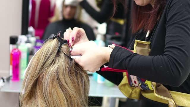 professional female hairdresser applying color to female customer at the hair salon, - highlights hair stock videos & royalty-free footage