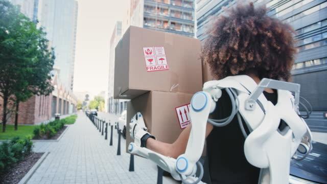 動力外骨格のプロの女性のホームの引っ越し業者。トラックから重い箱を拾う - 段ボール箱点の映像素材/bロール