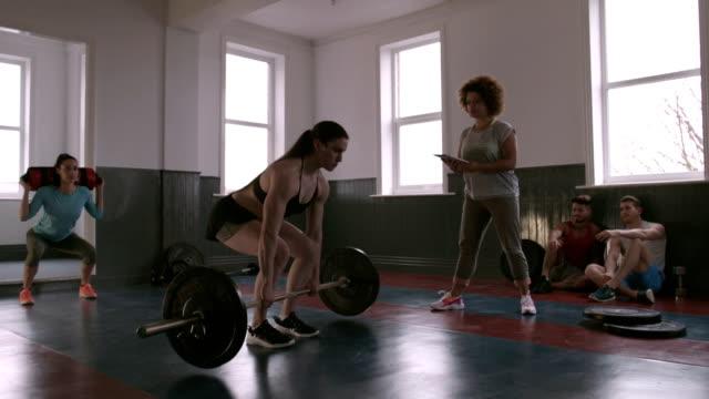 stockvideo's en b-roll-footage met professionele vrouwelijke powerlifter deadlifting zware gewicht - gewichtheffen krachttraining