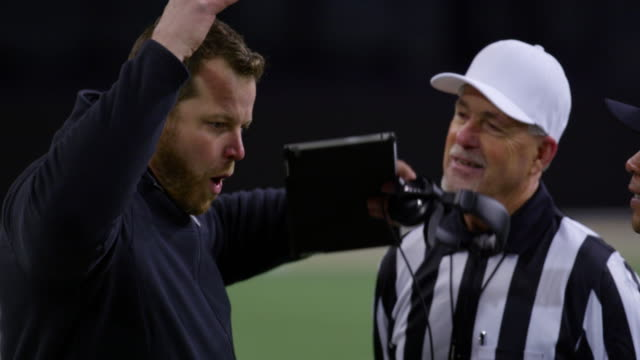 MS Professional football coach arguing with referees on sideline during game