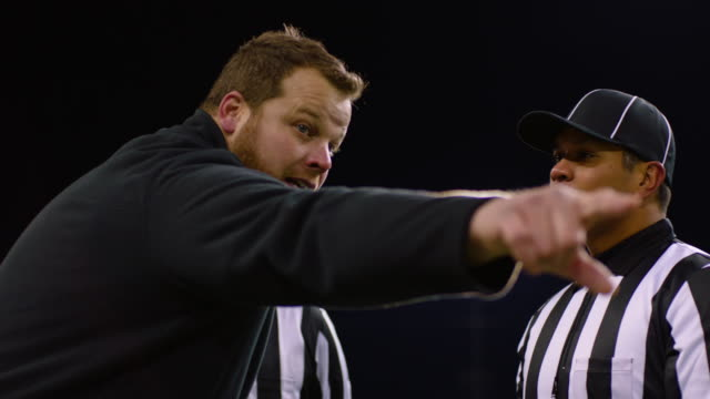 MS DS SLO MO Professional football coach arguing with referees on sideline during game