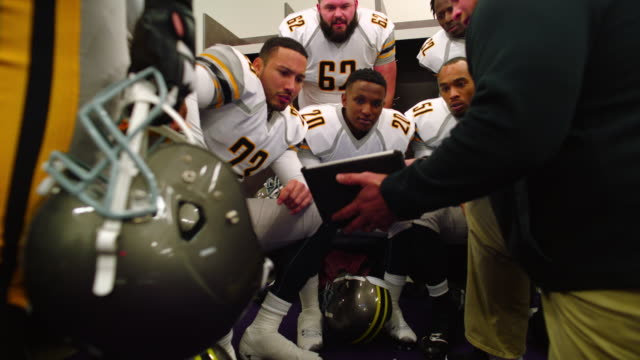 MS LA Professional football coach in locker room with team before game reviewing plays on digital tablet