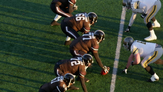 MS TS Professional football offensive linemen coming to line of scrimmage and snapping football