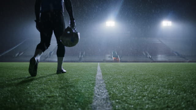 ws slo mo. professional football player carries helmet and walks off field as rain falls in empty stadium. - shower stock videos & royalty-free footage