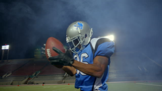MS SLO MO. Professional football player claps hands on ball in empty stadium.