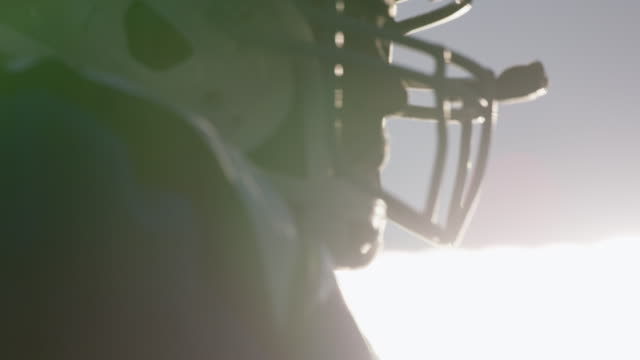 CU SLO MO. Professional football player in game helmet silhouetted by stadium lights.