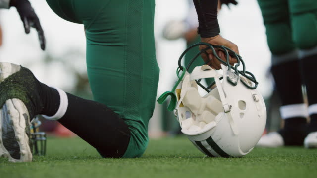 CU SLO MO. Professional football player kneels and grips helmet on playing field.