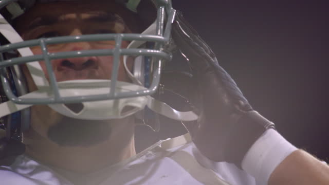 cu slo mo professional football player putting on helmet before running onto field - sports helmet stock videos & royalty-free footage