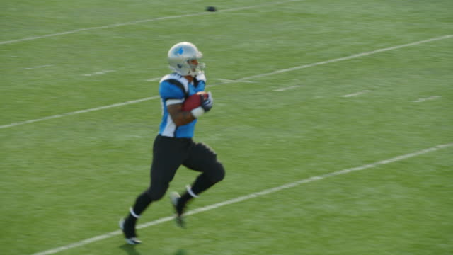 ws slo mo. professional football player runs with football, prances into end zone for touchdown, and jumps into the air with teammates. - アメフトのユニフォーム点の映像素材/bロール