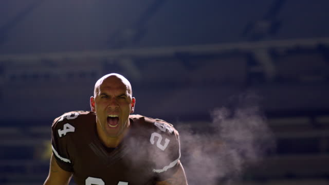 MS Professional football player screaming on field at night