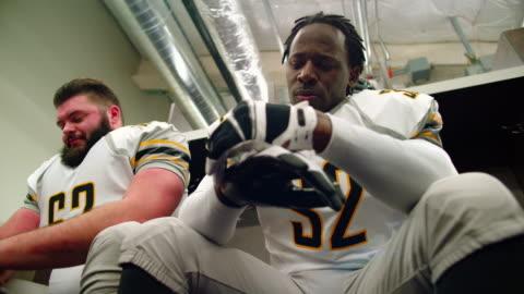 vidéos et rushes de ms la professional football player sitting in locker room with teammates putting on gloves before game - porte structure créée par l'homme