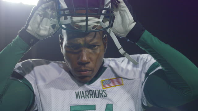 vídeos y material grabado en eventos de stock de cu slo mo. professional football player stares into camera and puts helmet on. - casco de deportes