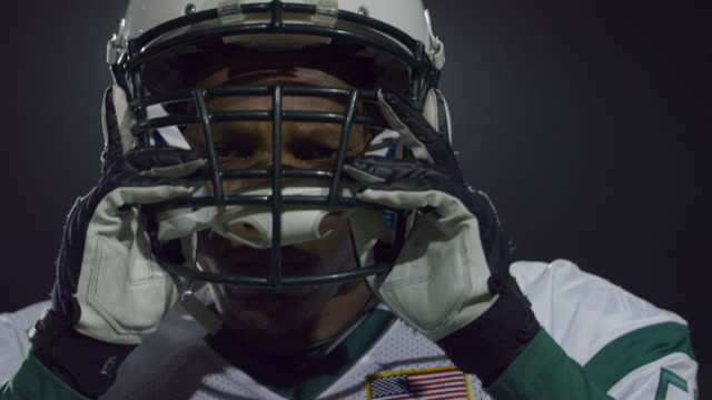 CU SLO MO. Professional football player stares into camera and takes helmet off.