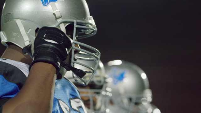 CU SLO MO. Professional football player straps and tightens helmet and roars.