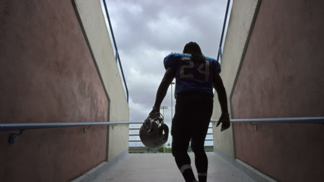 ws slo mo. professional football player walks out of tunnel carrying helmet and stops to survey stadium on game day. - football feld stock-videos und b-roll-filmmaterial