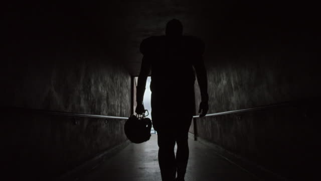 WS SLO MO. Professional football player walks through tunnel carrying helmet and stops to survey stadium before game.