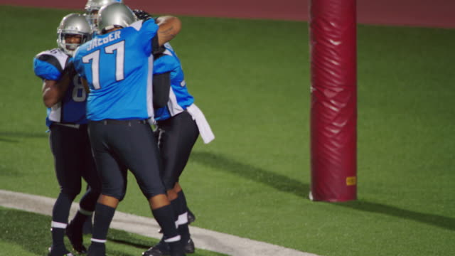 MS SLO MO. Professional football players celebrate touchdown with teammates in end zone.