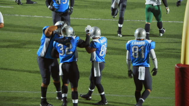 ws. professional football players celebrate touchdown with teammates in end zone. - アメフトのユニフォーム点の映像素材/bロール
