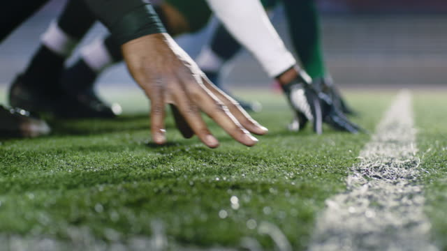CU SLO MO. Professional football players crouch and press hands into turf in three-point stance at line of scrimmage and spring into action on snap.