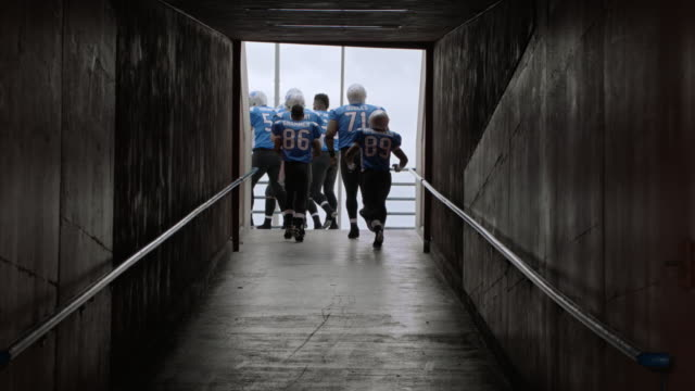 WS SLO MO. Professional football players enter stadium pumped up on game day.