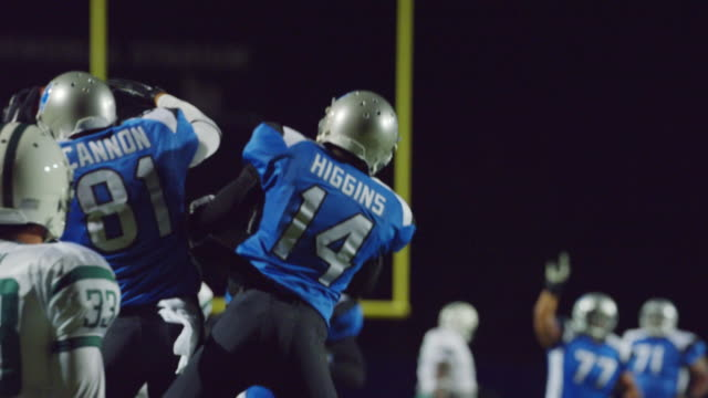 ms slo mo. professional football players jump up and embrace teammates in touchdown celebration. - american football sport stock videos & royalty-free footage