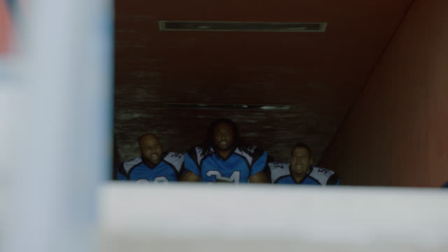 WS SLO MO. Professional football players run out of tunnel into stadium cheering on teammates and pumping up crowd on game day.