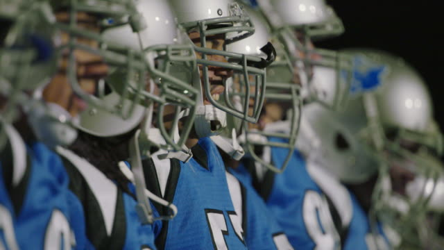 CU SLO MO. Professional football players stand in line at attention at start of game.