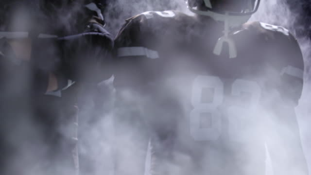 MS Professional football players standing together in fog on field before game