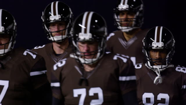 ms slo mo professional football players walking out of tunnel in football stadium before game - football player stock videos & royalty-free footage