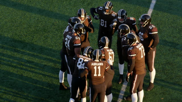 MS TS Professional football quarterback calling play in huddle and taking snap and throwing pass from shotgun position