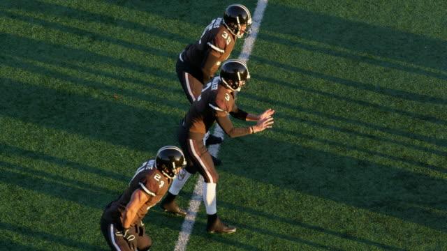 ms ts professional football quarterback taking snap from shotgun position and throwing pass - アメリカンフットボールヘルメット点の映像素材/bロール