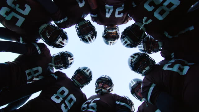 ms la pov slo mo professional football team coming in to huddle - チームワーク点の映像素材/bロール