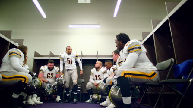 MS LA SLO MO Professional football team getting motivated and jumping up and down in locker room before game