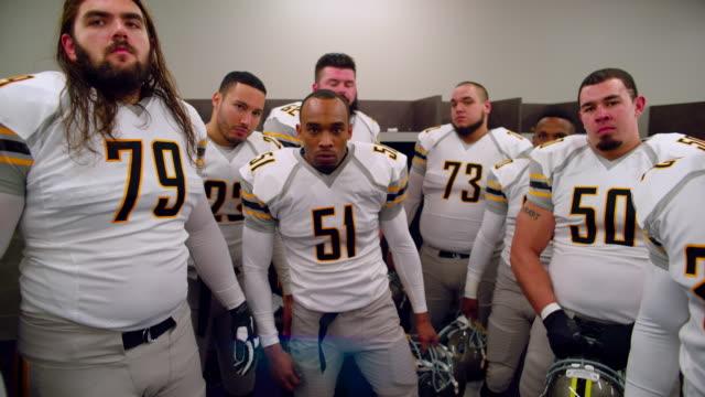 ms ds slo mo professional football team getting motivated in locker room before heading onto field - sportmannschaft stock-videos und b-roll-filmmaterial